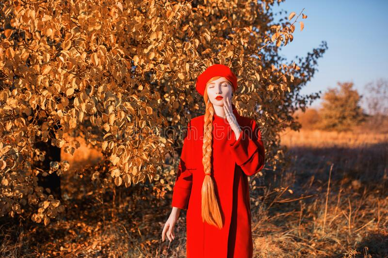 Redhead woman with long hair in red coat on autumn background. Girl with long braided plait on background of forest with orange stock images