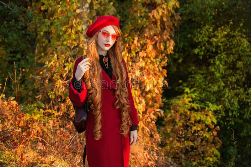 Redhead woman with long hair in red coat on autumn background. Redhead girl in sunglasses on background of forest. Autumn clothes royalty free stock photography