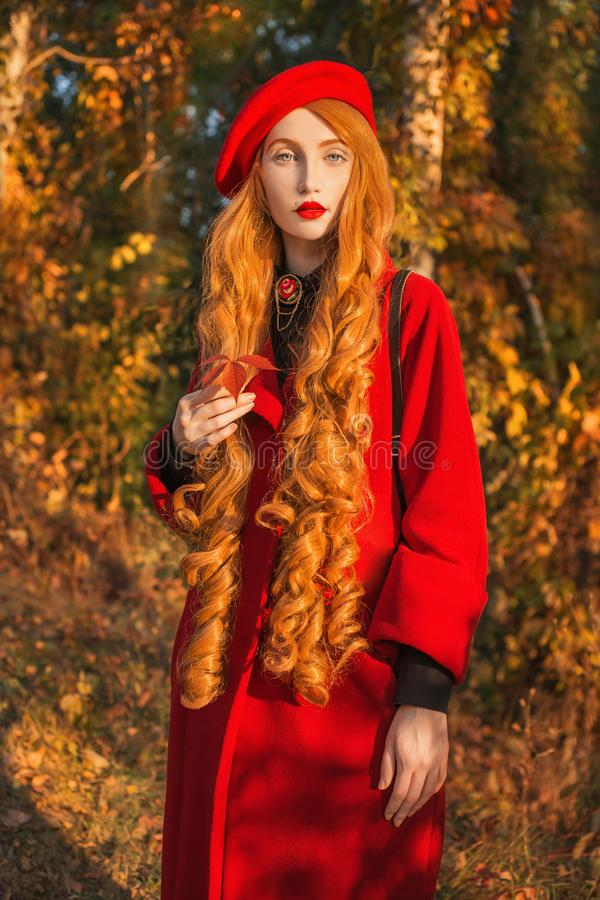 Redhead woman with long wave hair in red coat on autumn background. Girl on background of forest with orange autumn leaves. Leaves. Fall from branches in stock photos