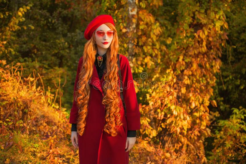 Redhead woman with long wave hair in red coat on autumn background. Girl on background of forest with orange autumn leaves. Model. With pink sunglasses. Leaves stock photography