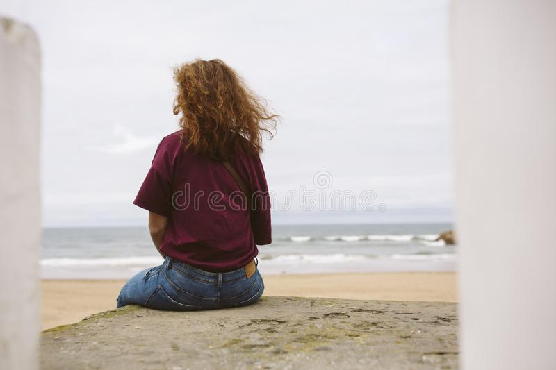 Redhead woman looking at the landscape of a beach. Redhead woman looking at the landscape of a beach in Morocco stock photo