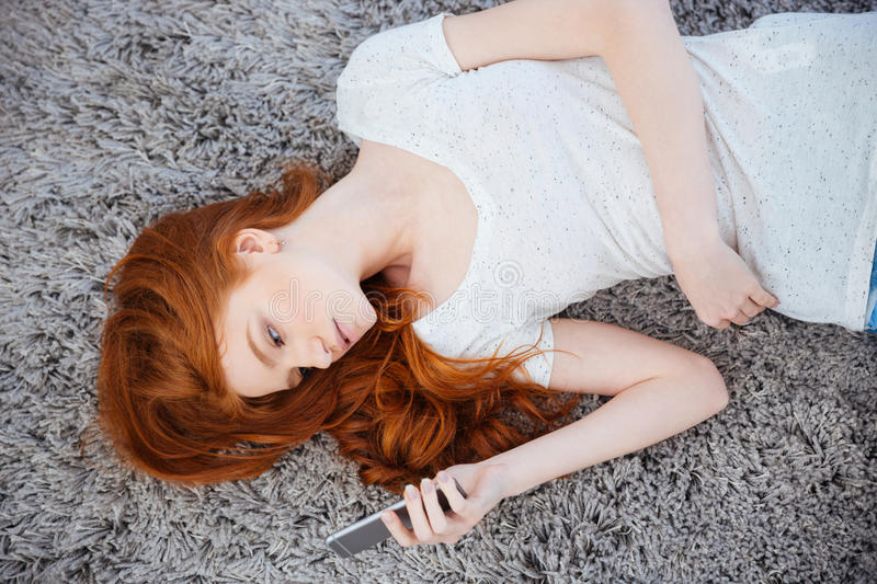 Redhead woman lying on the carpet with smartphone stock images