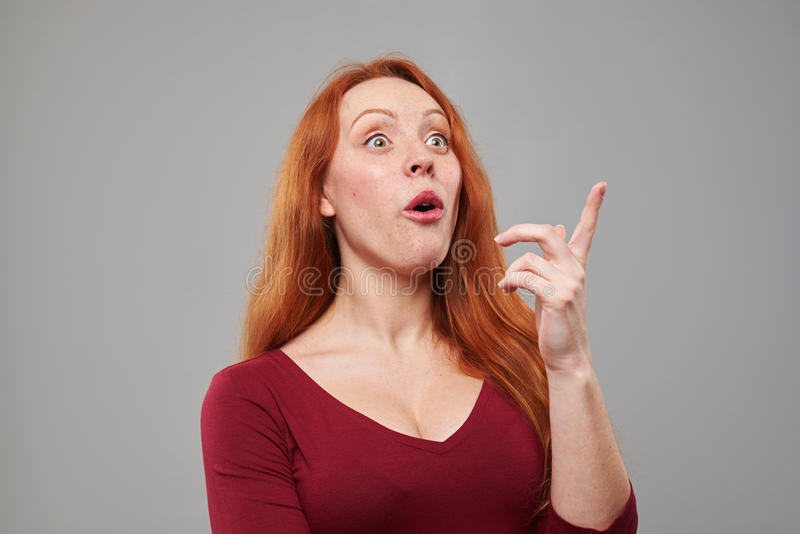 Redhead woman noticed something upwards. Close-up of redhead woman noticing something upwards. Pointing with index finger. Woman in amazement royalty free stock photo