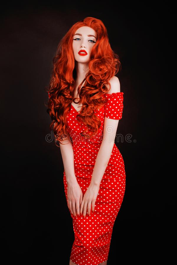 Redhead woman with pale skin and red lips on black background. Girl with copper hair in retro dress. Red curly wig. Redhead woman royalty free stock photos