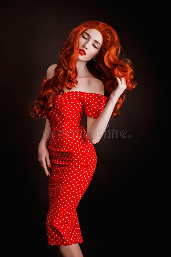 Redhead woman with pale skin and red lips on black background. Girl with copper hair in retro dress. Red curly wig. Redhead woman stock photography
