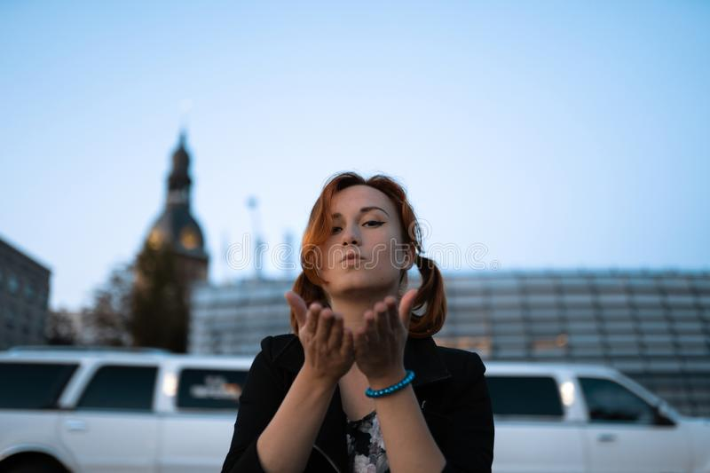 Redhead woman portrait in front of a glass building - Traveler and explorer royalty free stock photography