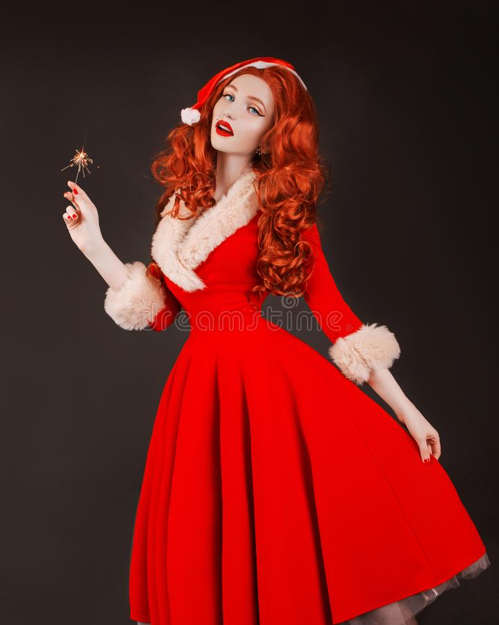 Redhead woman in red christmas dress in hat on black background. Sexy santa girl with bengal firework in hand. New year concept. Happy model with long hair stock photos
