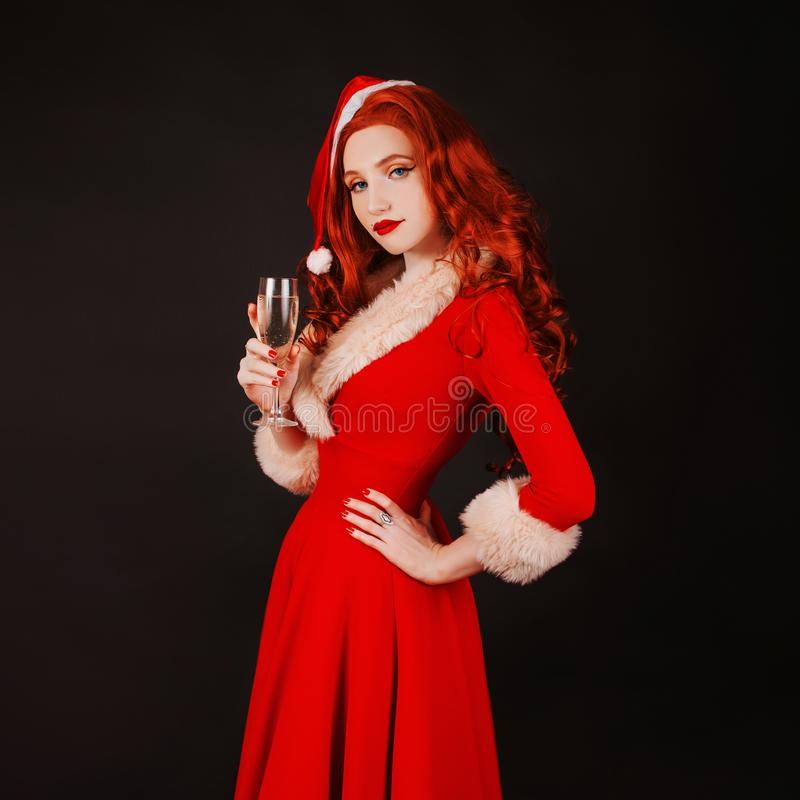 Redhead woman in red christmas dress in hat on black background. Sexy santa girl with glass of champagne in hand. New year concept. Model with glass of alcohol stock image