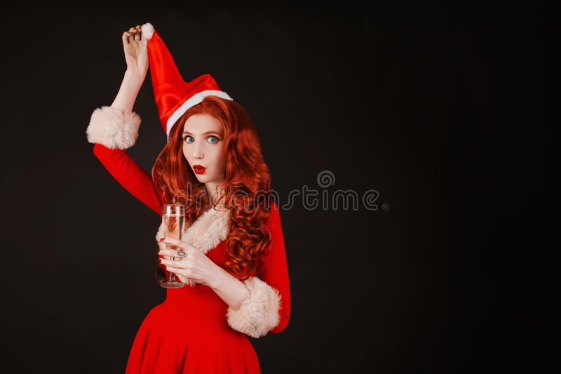 Redhead woman in red christmas dress in hat on black background. Sexy santa girl with glass of champagne in hand. New year concept. Model with glass of alcohol royalty free stock image