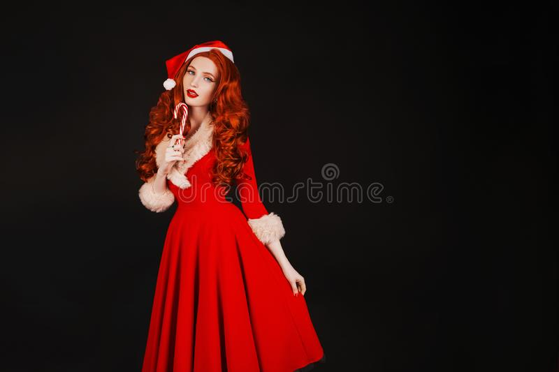 Redhead woman in red christmas dress in hat on black background. Sexy santa girl licking lollipop. New year copyspace. Beautiful. Model with long hair royalty free stock images