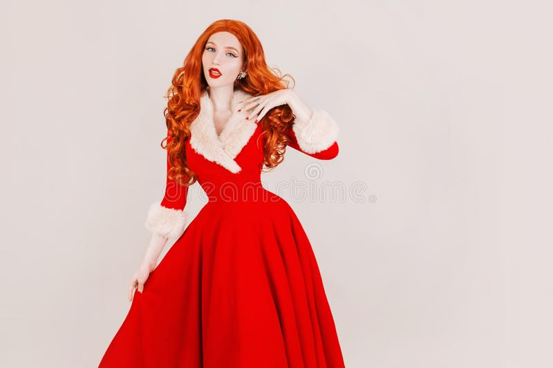 Redhead woman in red christmas dress isolated on white background. Sexy santa girl. New year concept. Celebrate New Year. Christmas sale copyspace. Red hair stock photo