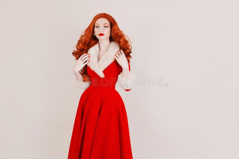 Redhead woman in red christmas dress  on white background. Sexy santa girl. New year concept. Celebrate New Year. Christmas sale. Red hair model. Copy space royalty free stock photography