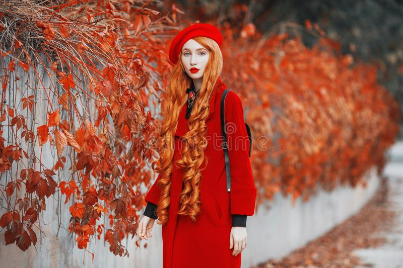 Redhead woman in red coat on autumn background. Girl on background of forest with orange autumn leaves. Leaves fall from branches. In october. Red turban and royalty free stock photo