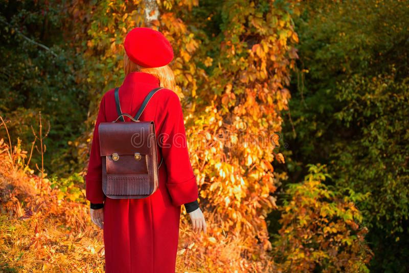Redhead woman in red coat on autumn background. Girl with bag on background of forest with orange autumn leaves. Leaves fall from. Branches in october. Red stock photography