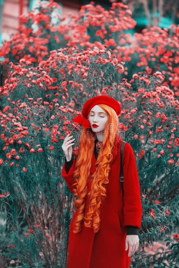 Redhead woman in red coat on garden background. Fashion model with long red hair with flower in hand. Red turban and stylish coat. Stylish model royalty free stock image