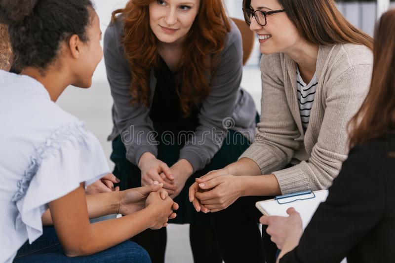 Redhead woman supporting friend during psychotherapy group meeting royalty free stock images