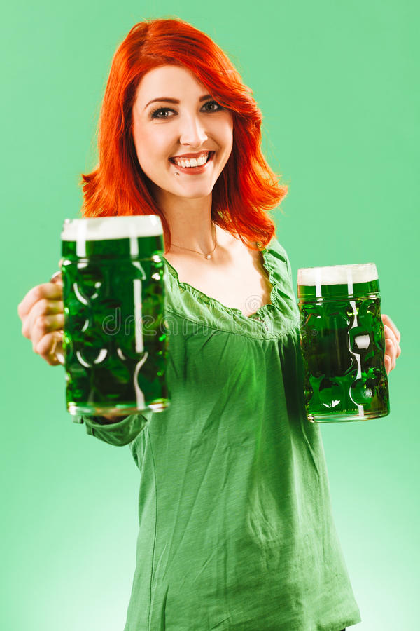 Redhead woman with two huge green beers. Photo of a beautiful redhead woman holding and drinking two huge green beers on St Patricks Day royalty free stock photos