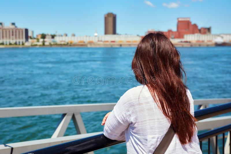 Redhead woman watching the scenery of Montreal city and the Saint Lawrence river on a sunny summer day in Quebec, Canada. Facing back redhead female watching the stock image