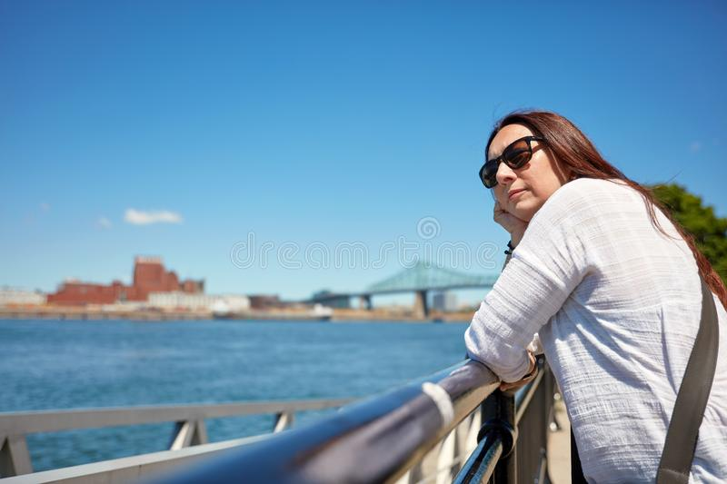 Redhead woman watching the scenery of Montreal city and the Saint Lawrence river on a sunny summer day in Quebec, Canada. Redhead female with sunglasses watching royalty free stock photography