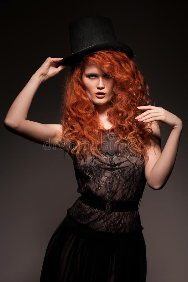 Redhead woman wearing black bowler hat royalty free stock photos