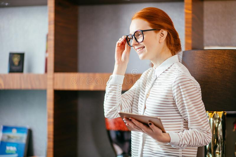 Redhead smiling young female manager using modern digital tablet at office royalty free stock photos
