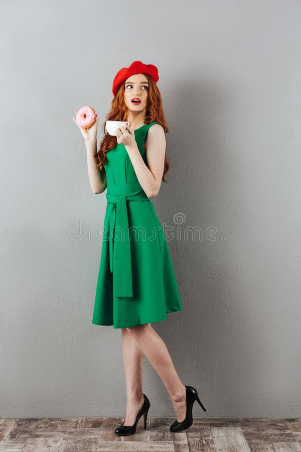 Redhead young cute lady eating donut and drinking coffee. stock photography