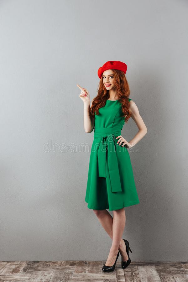 Redhead young happy lady pointing to copyspace. stock photo