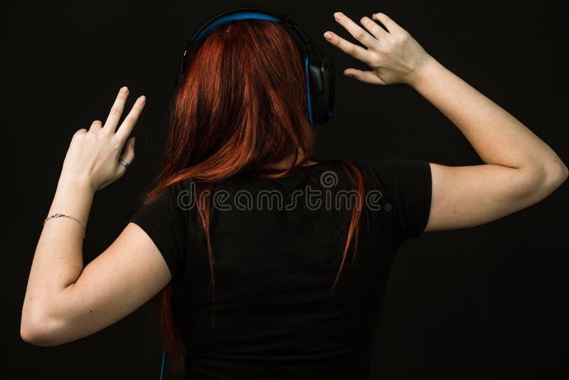 Redheaded женщина с голубыми наушниками танцует стоковое фото