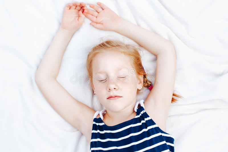 redheaded Caucasian child girl in striped nautical sleeveless shirt sleeping stock photo