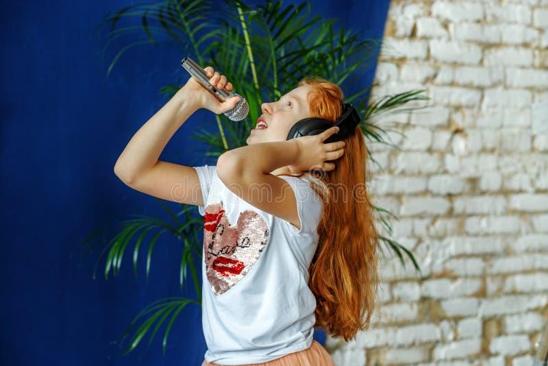 Redheaded dzieciak słucha muzyka i śpiew Pojęcie jest chi zdjęcie royalty free