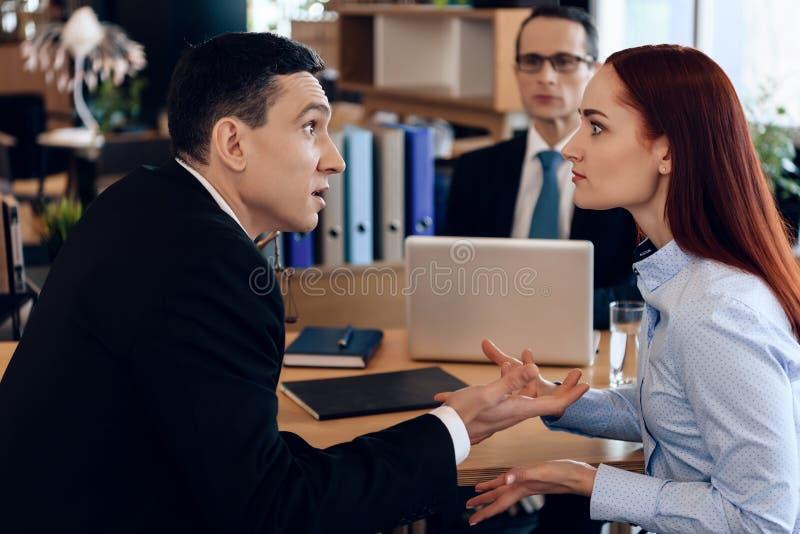 Redheaded Frau argumentiert mit erwachsenem Mann in Scheidungsanwalt ` s Büro lizenzfreies stockfoto