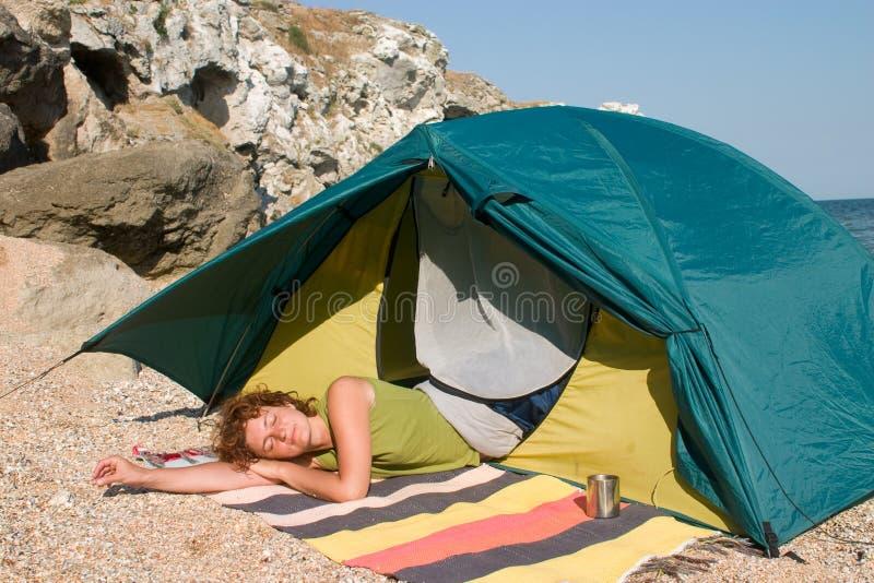 Redheaded Frau, die im Zelt am Seestrand schläft stockfotografie