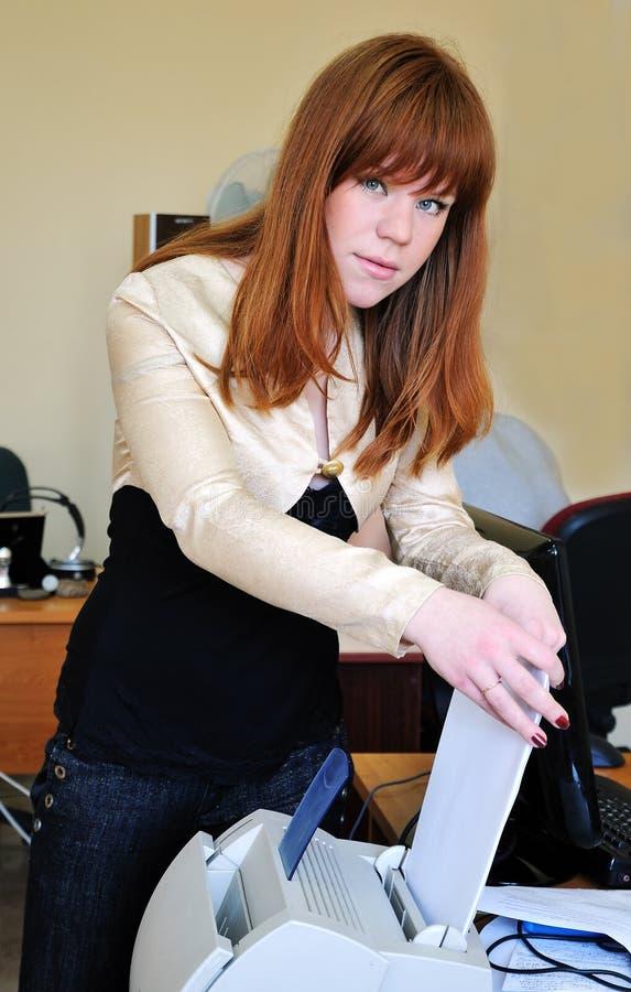 Redheaded girl using printer stock photos