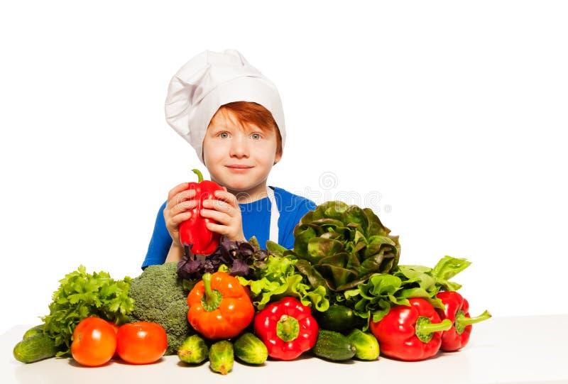 Redheaded jongen in eenvormige de holdings Spaanse peper van de kok royalty-vrije stock foto's