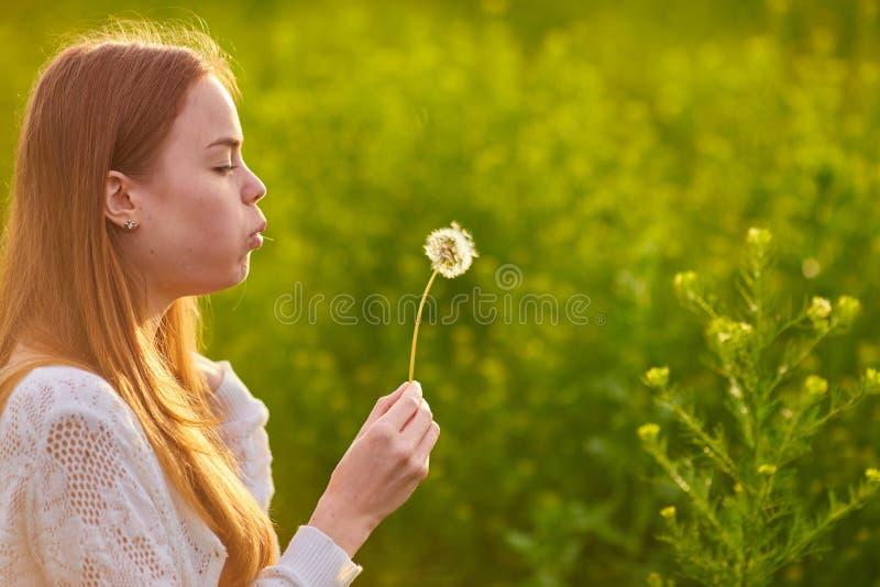 Redheaded jugendlich Mädchen, das auf Löwenzahn durchbrennt lizenzfreies stockbild