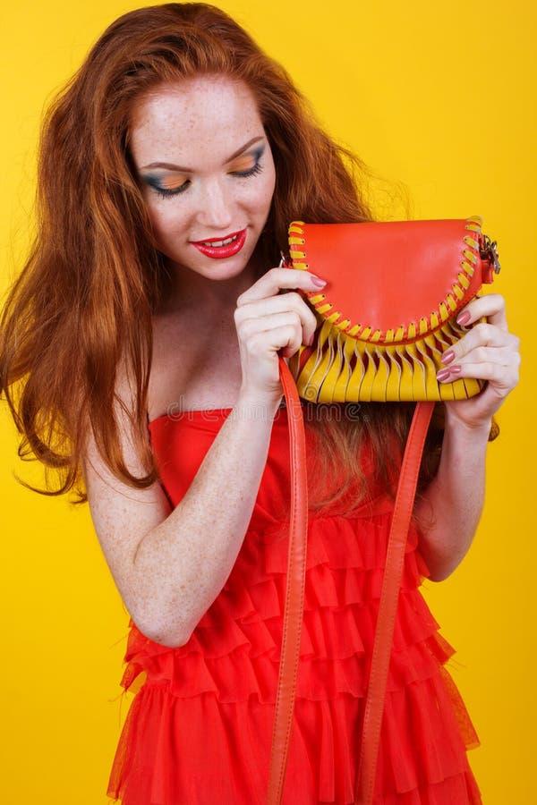 Redheaded le flicka med den orange handväskan arkivfoton