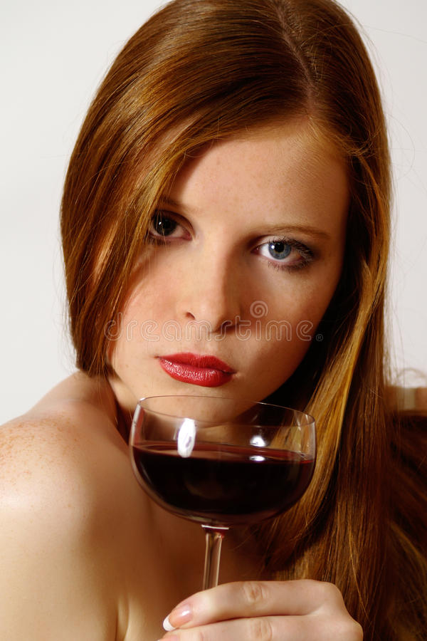 Redheaded Mädchen mit Glasrotwein stockfoto