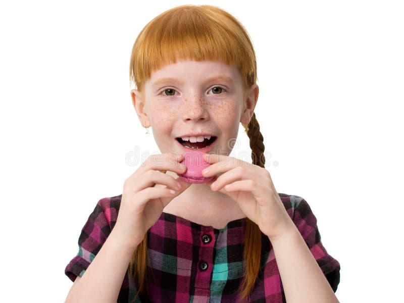 Redheaded meisje met sproeten opende haar mond en wil macaron roze cak eten stock afbeeldingen