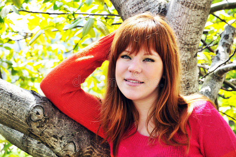 Redheaded meisje onder de boom stock foto