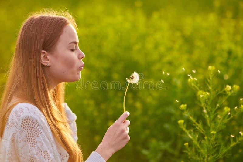 Redheaded nastoletni dziewczyny dmuchanie na dandelions fotografia royalty free