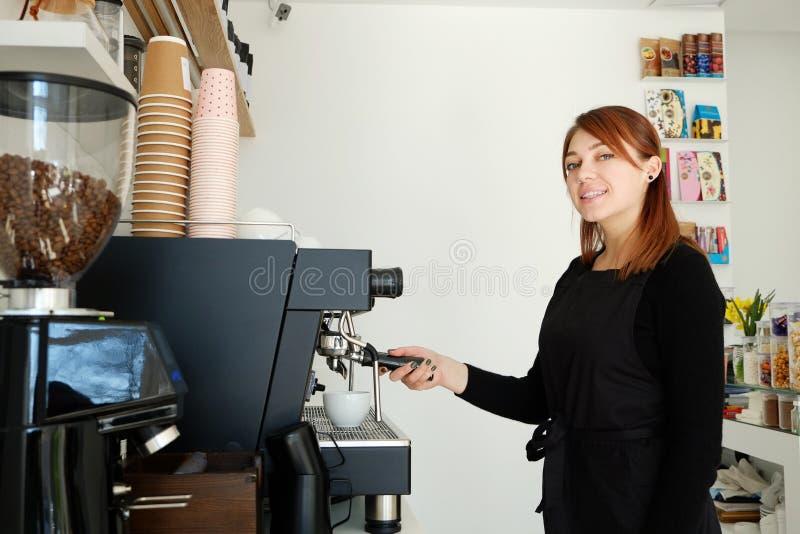 Redheaded ung kvinna som arbetar i coffee shop som prepearing en drink royaltyfri foto