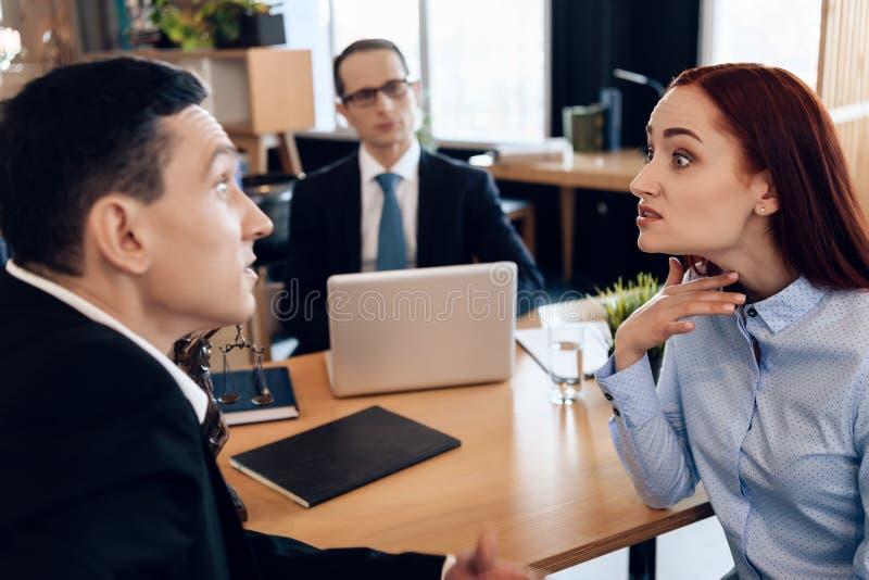 Redheaded verärgerte Frau argumentiert mit erwachsenem Mann in Scheidungsanwalt ` s Büro lizenzfreies stockfoto