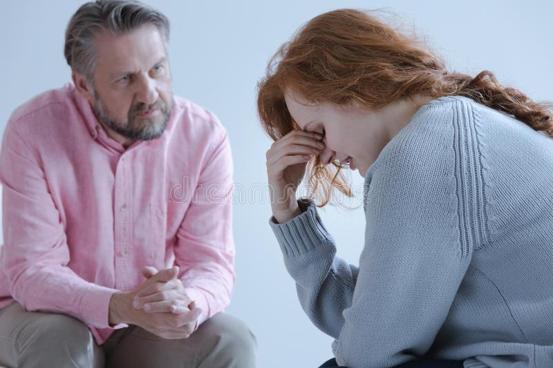 A redheaded young woman with a post traumatic stress disorder. A redheaded young women with a post traumatic stress disorder touching her eyes with her hand royalty free stock image
