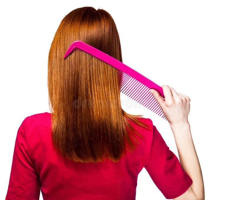 Redheadflicka med den stora hårkammen royaltyfria foton