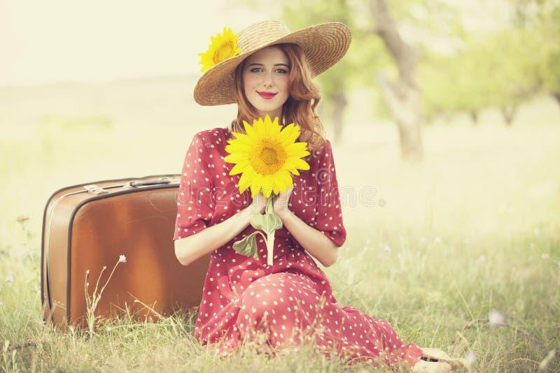 Redheadflicka med solrosen på utomhus-. royaltyfri foto