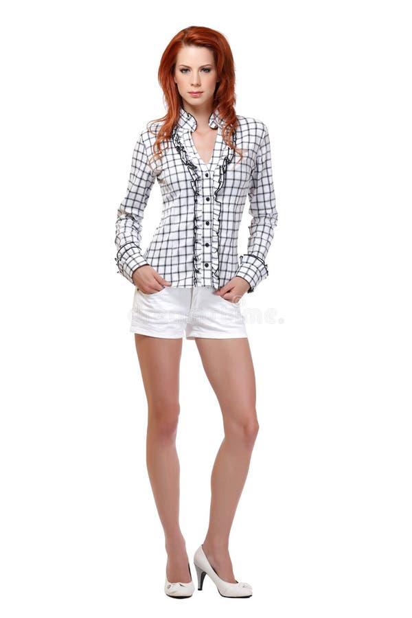 Redheadfrau, die auf weißem Hintergrund aufwirft lizenzfreie stockfotos