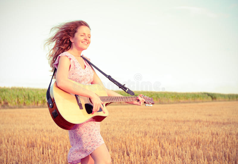 Redheadfrau, die Gitarre spielt lizenzfreies stockbild