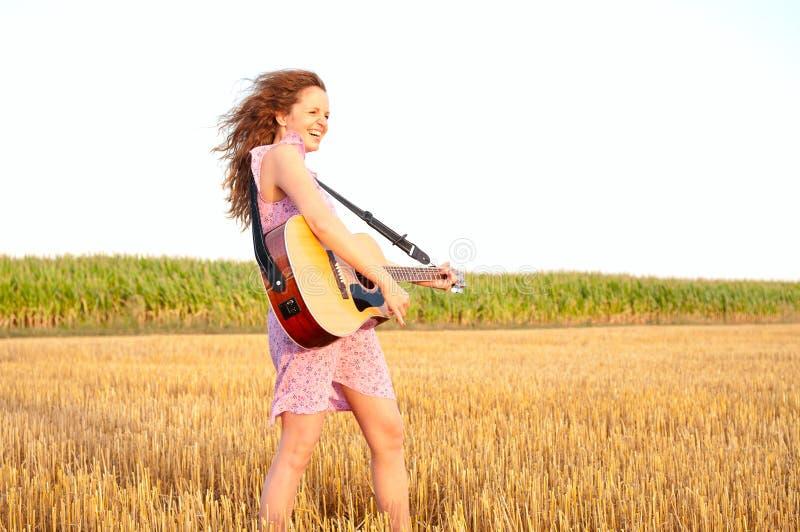 Redheadfrau, die Gitarre spielt lizenzfreie stockfotografie