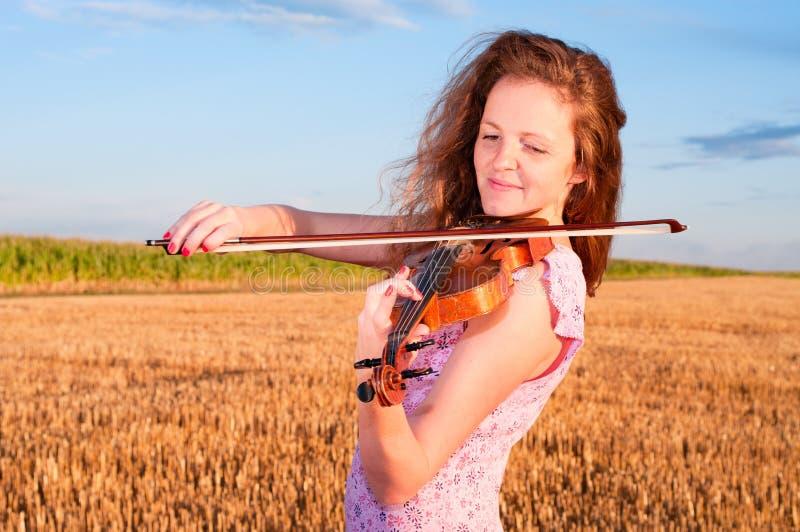 Redheadfrau, die Violine spielt stockfoto