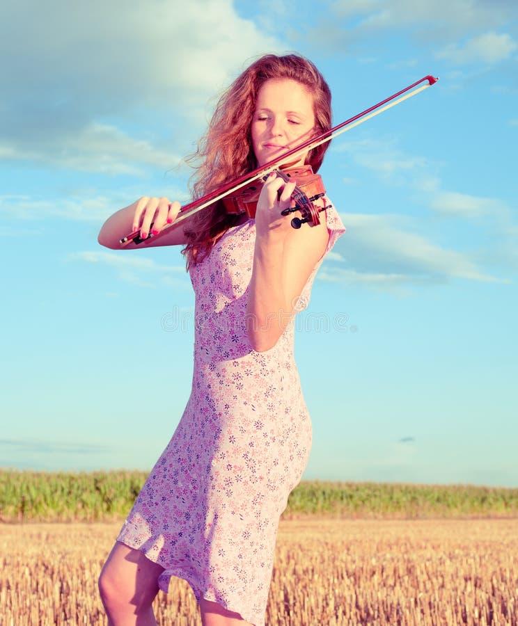 Redheadfrau, die Violine spielt stockfotos